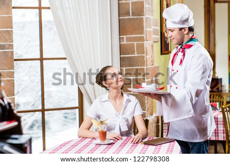 Chef brings a dish pretty woman in a restaurant, a pleasant time forwarding - stock photo