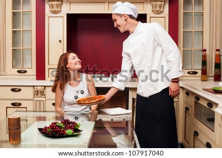 Chef brings the pizza to the client - stock photo