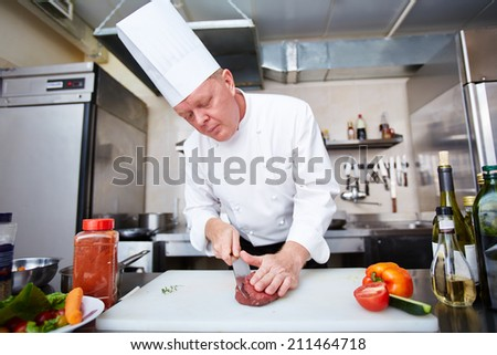 Chef carving meat at the kitchen - stock photo