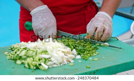 Chef Chopping Vegetables. Chef at work in restaurant kitchen. Chef Chopping Salad Ingredients.Food preparation. - stock photo