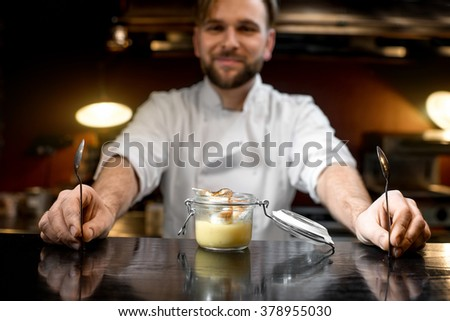 Chef cook serving lemon dessert on the bar table at the restaurant. Image focused on the jar with small depth of field - stock photo