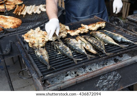 Chef cookind at grill grate. Plenty of chicken tabaka and mackerel fish grilled at barbecue. Mackerel and whole chicken bbq outdoors at picnic, party. Street food, meat and fish grill takeaway - stock photo