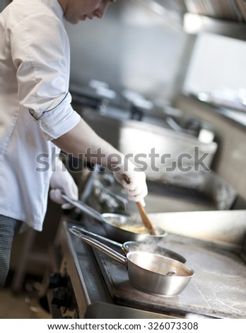 chef cooking in the kitchen. focus on the pot of steam