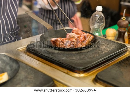 Chef cooking meat over a commercial hotplate or griddle with a pair of tongs in a restaurant, close up view of his hands and the portions of meat - stock photo