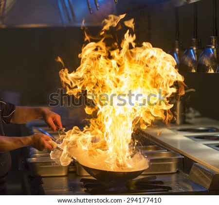 Chef cooking with flame - stock photo