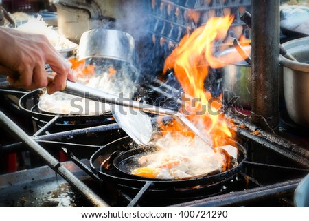 Chef cooking with flame in a frying pan - stock photo