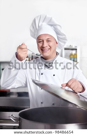 Chef cooks in the kitchen - stock photo