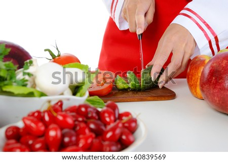 Chef cuts the cucumber. Isolated on white background - stock photo