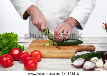 Chef cutting a green cucumber in his kitchen - stock photo