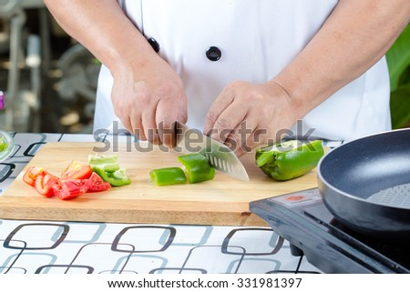 Chef cutting bell pepper and vegetable on cutting board