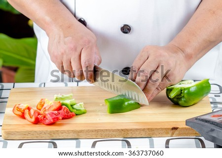 Chef cutting bell pepper and vetgetable on cutting board