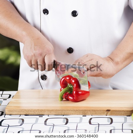 Chef cutting red bell pepper on wooden broad - stock photo