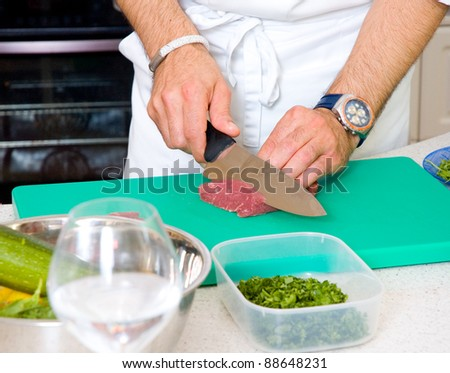 Chef cutting the meat on a board - stock photo