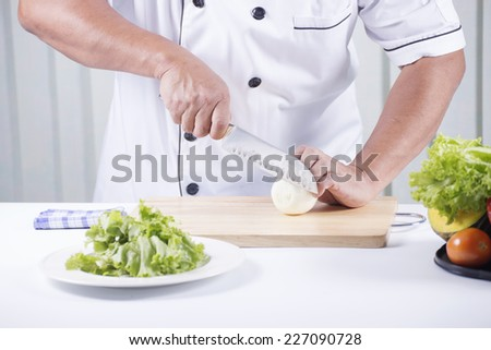 Chef cutting the onion on a wooden board/Making Salad concept