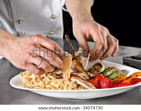 Chef decorate plate with pasta and fried fish