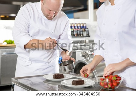 Chef decorates dessert cake with chocolate sauce in kitchen - stock photo