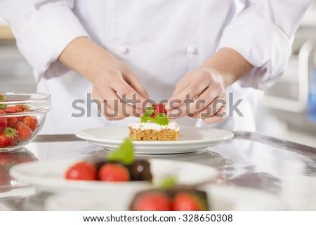 Chef decorates dessert cake with strawberry - stock photo
