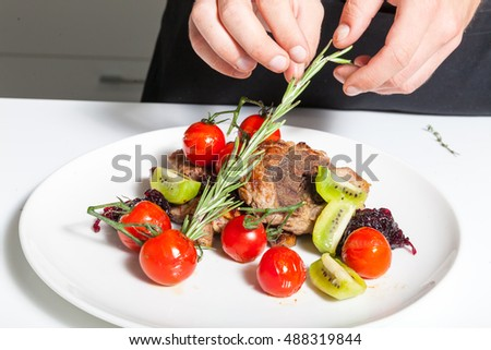 Chef decorating meat dish