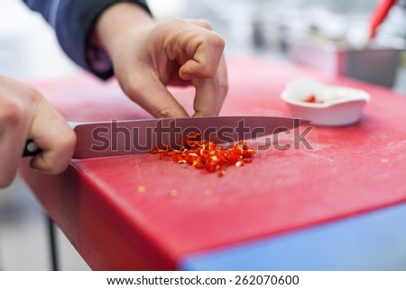 Chef dicing red hot chili peppers on a chopping board in a commercial kitchen for use as a spicy flavouring in his recipes as he cooks the evening meal - stock photo
