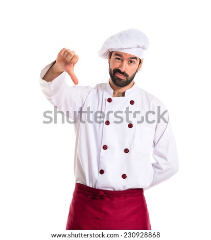 Chef doing a bad signal over white background - stock photo