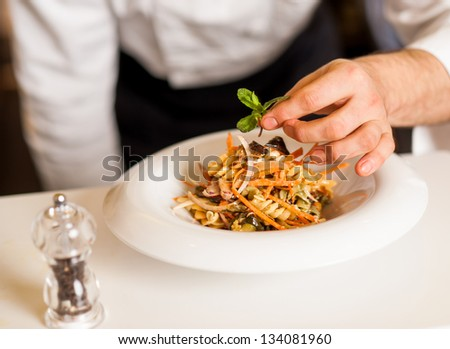 Chef dressed in white uniform decorating pasta salad, cropped image. - stock photo
