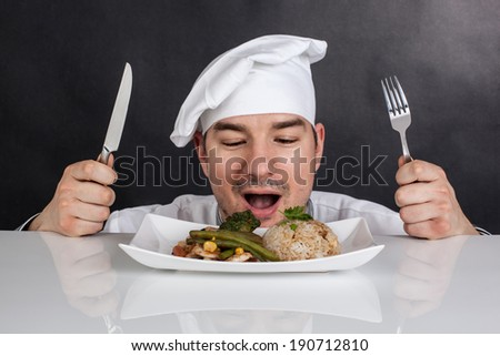 Chef eating his prepared food with cutlery. Black background - stock photo