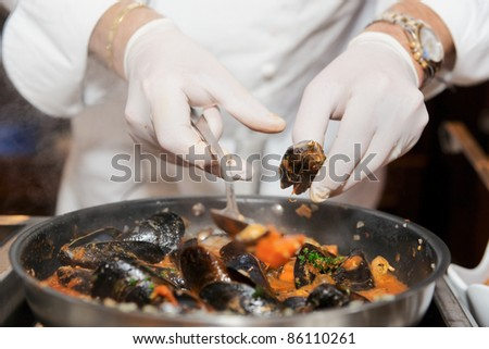 Chef frying mussels on commercial kitchen in restaurant, close-up on hands