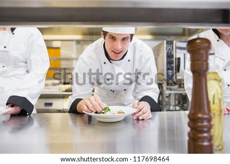 Chef garnishing his salad and smiling in the kitchen - stock photo