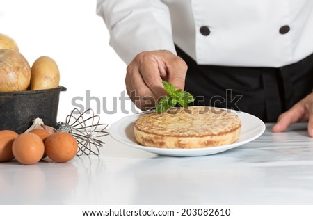 Chef garnishing with mint leaves one potato omelette - stock photo