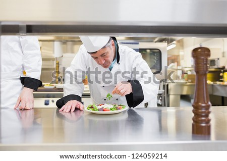 Chef garnisning his salad in kitchen - stock photo