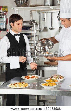 Chef giving customer's food to waiter in restaurant kitchen - stock photo