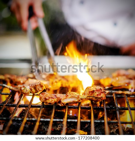 chef grilling lamb ribs on flame - stock photo