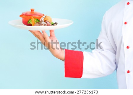 Chef hand serving food on blue concert wall  - stock photo