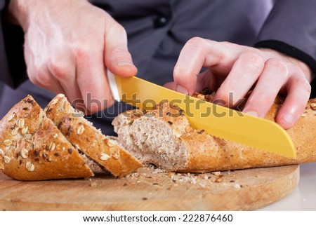 chef hand with a knife, sliced bread on a cutting board  - stock photo