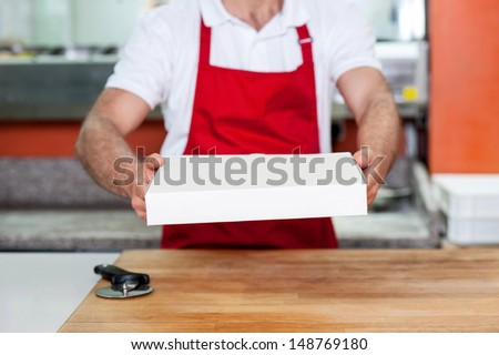 Chef handing over pizza, cropped image. - stock photo
