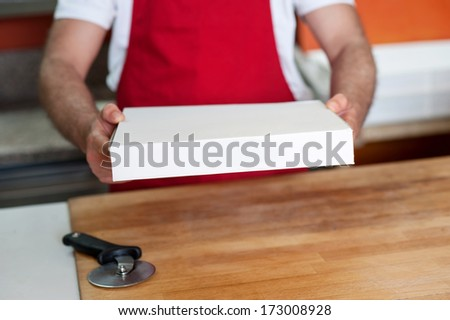 Chef handing over pizza, cropped image - stock photo