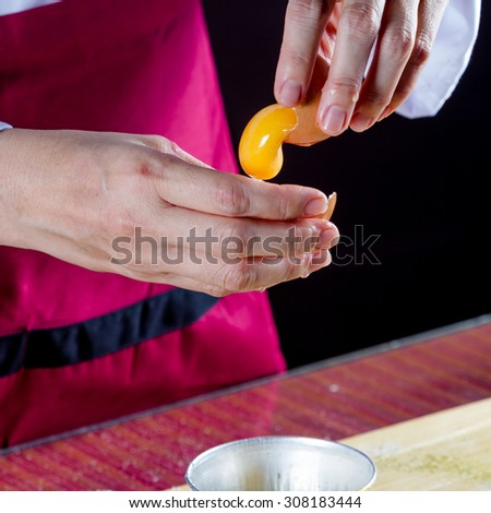 Chef hands cracking an egg into a glass bowl