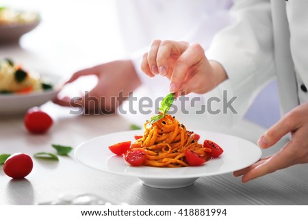 Chef hands preparing delicious cold pasta salad on the table closeup - stock photo