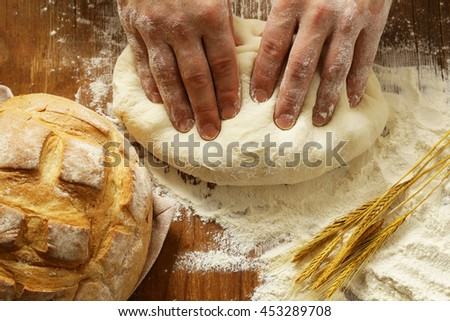 Chef hands with dough and homemade natural organic bread and flour on a wooden background - stock photo