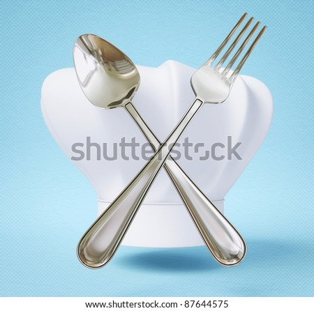 chef hat with spoon and fork isolated on a blue - stock photo