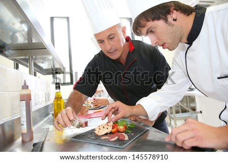 Chef helping student in catering to prepare foie gras dish - stock photo