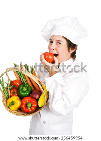 Chef holding a basket of fresh vegetables takes a bit out of a ripe tomato.  Isolated on white.   - stock photo