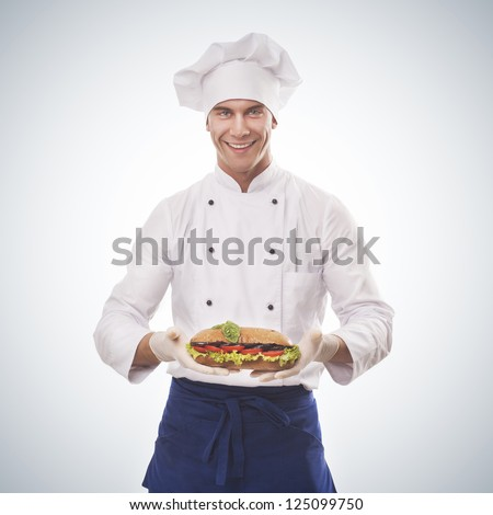 Chef holding a big sandwich isolated on blue gradient background - stock photo