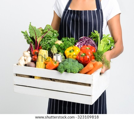 Chef holding a crate full of raw fresh organic vegetables on grey background, promoting eating seasonally and sourcing from local producers