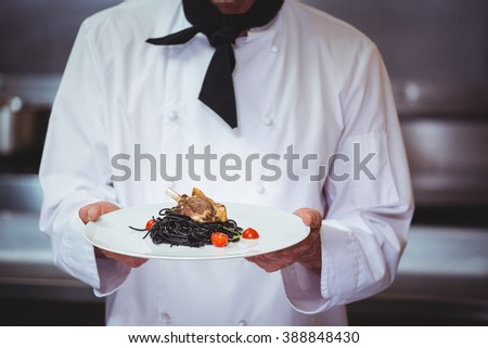 Chef holding a dish with spaghetti in commercial kitchen - stock photo