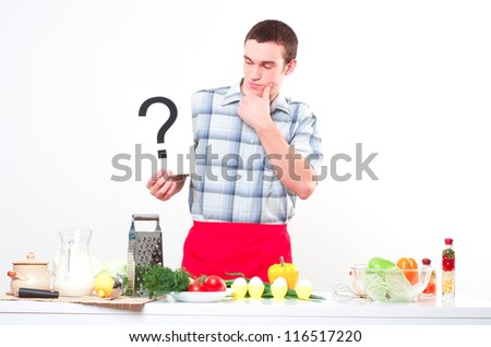 Chef holding a plate with an inscription question  mark - stock photo