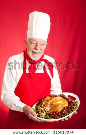Chef holding a Thanksgiving or Christmas turkey stuffed on a platter.