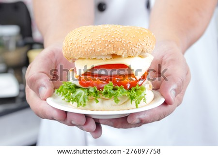 chef holding american cheese burger with fresh salad
