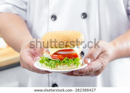 chef holding american cheese burger with fresh salad and french fries