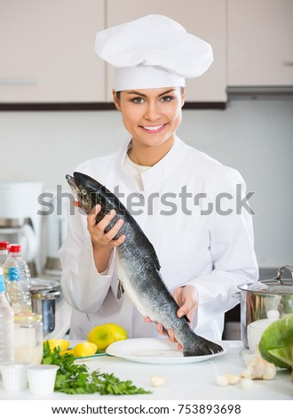 Chef holding carcass of rainbow trout in professional kitchen